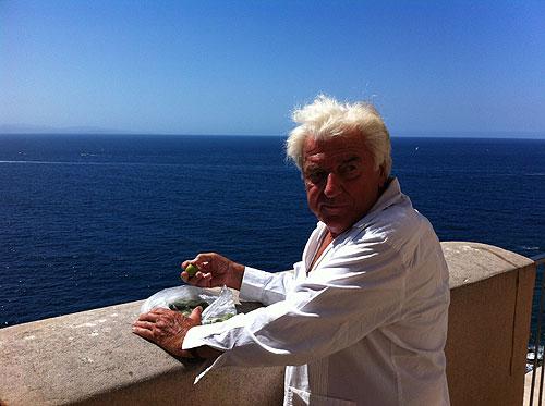 Christian Imbert eating mirabelles in Bonifacio, with Sardinia in the distance